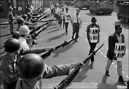 "29 Mar 1968, Memphis, Tennessee, USA --- National Guard bayonets block Beale Street as African-American protesters march through downtown Memphis wearing placards reading ""I  A MAN."" The previous day's march had broken out in rioting and looting, with one killed and 70 injured. Rev. Martin Luther King, Jr., who had left town after the first march, would soon return and be assassinated. --- Image by © Bettmann/CORBIS"