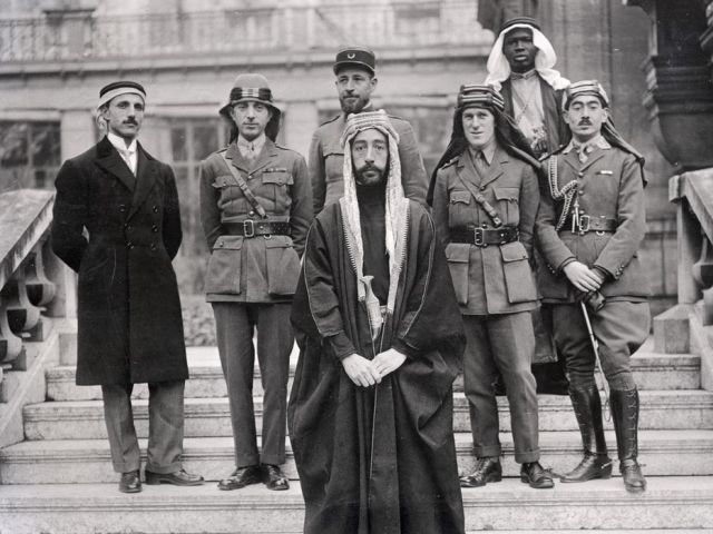 Faisal ibn Hussein's party at Versailles during the Paris Peace Conference of 1919. Left to right: Rustum Haidar, Nuri as-Said, Prince Faisal (front), Captain Pisani (rear), T.E. Lawrence, Faisal's servant (name unknown), Captain Hassan Khadri