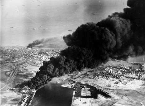 Smoke rises from oil tanks beside the Suez Canal hit during the initial Anglo-French assault on Port Said, November 5, 1956.
